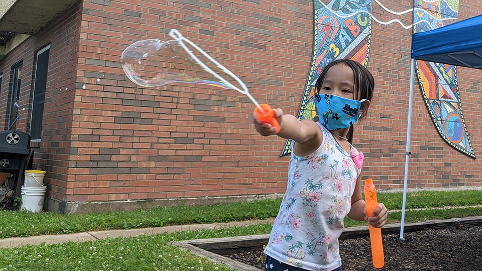 Girl making bubbles at Bayview Townhouses