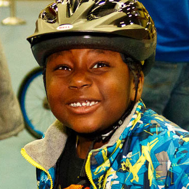 Child in bike helmet smiling