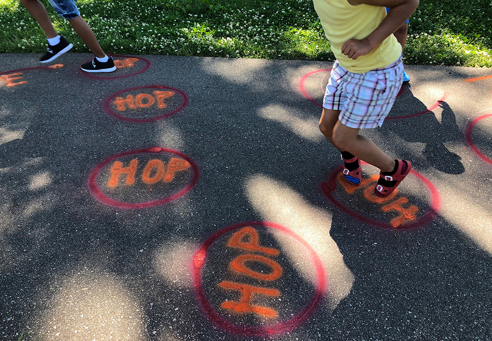 Children hopping through a course in Madison Children's Museum's Sidewalk Surprises program